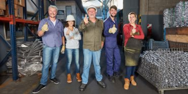 Group of successful workers in metallurgy factory hold thumbs up